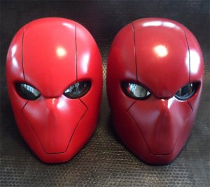 2 red hood helmets sitting side by side