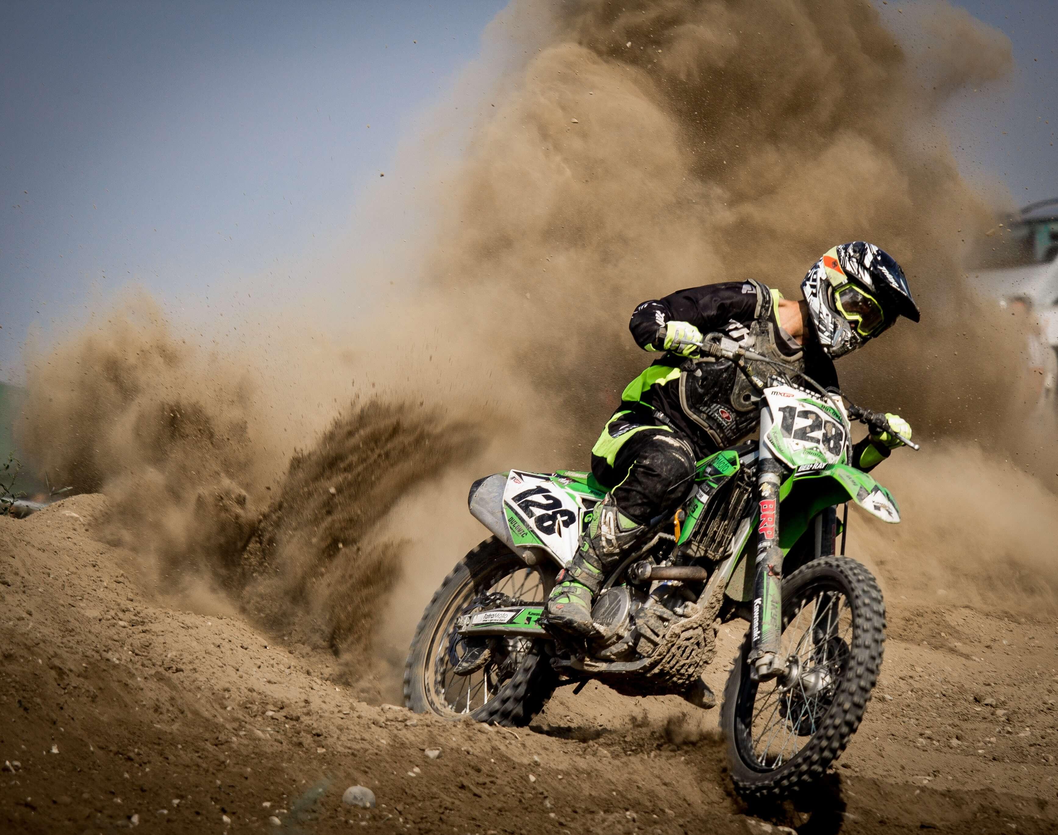 Dirt bike rider riding kicking up dirt
