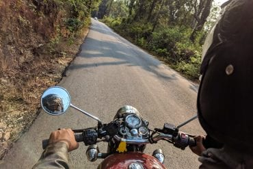 A motorcyclist wearing a helmet while riding on a paved road.