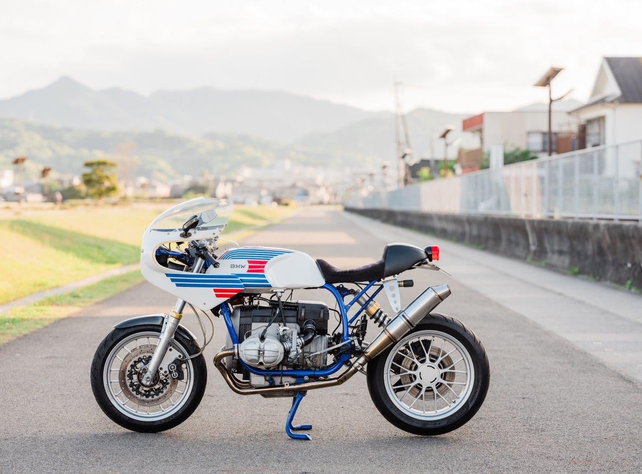 Retro BMW Racing Motorcycle on a footpath at sunset