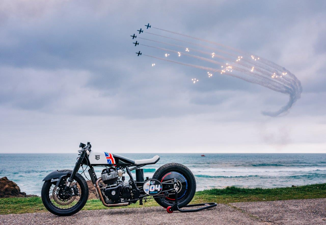 Royal Enfield sprint racing motorcycle on Biarritz beach with jet aircraft doing fly-by