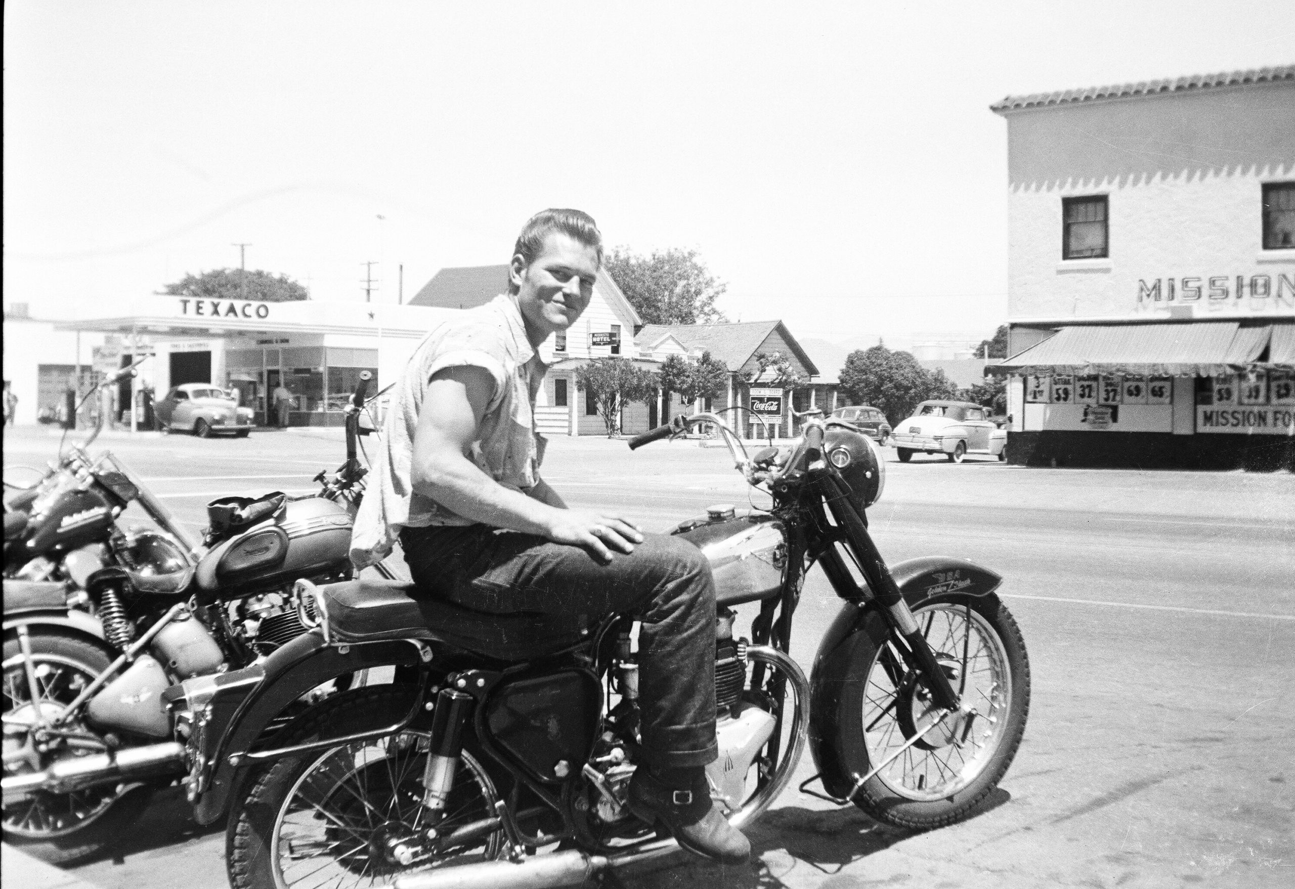 Two male riders pose for a photo on a street in Hollister, CA. in July 1947