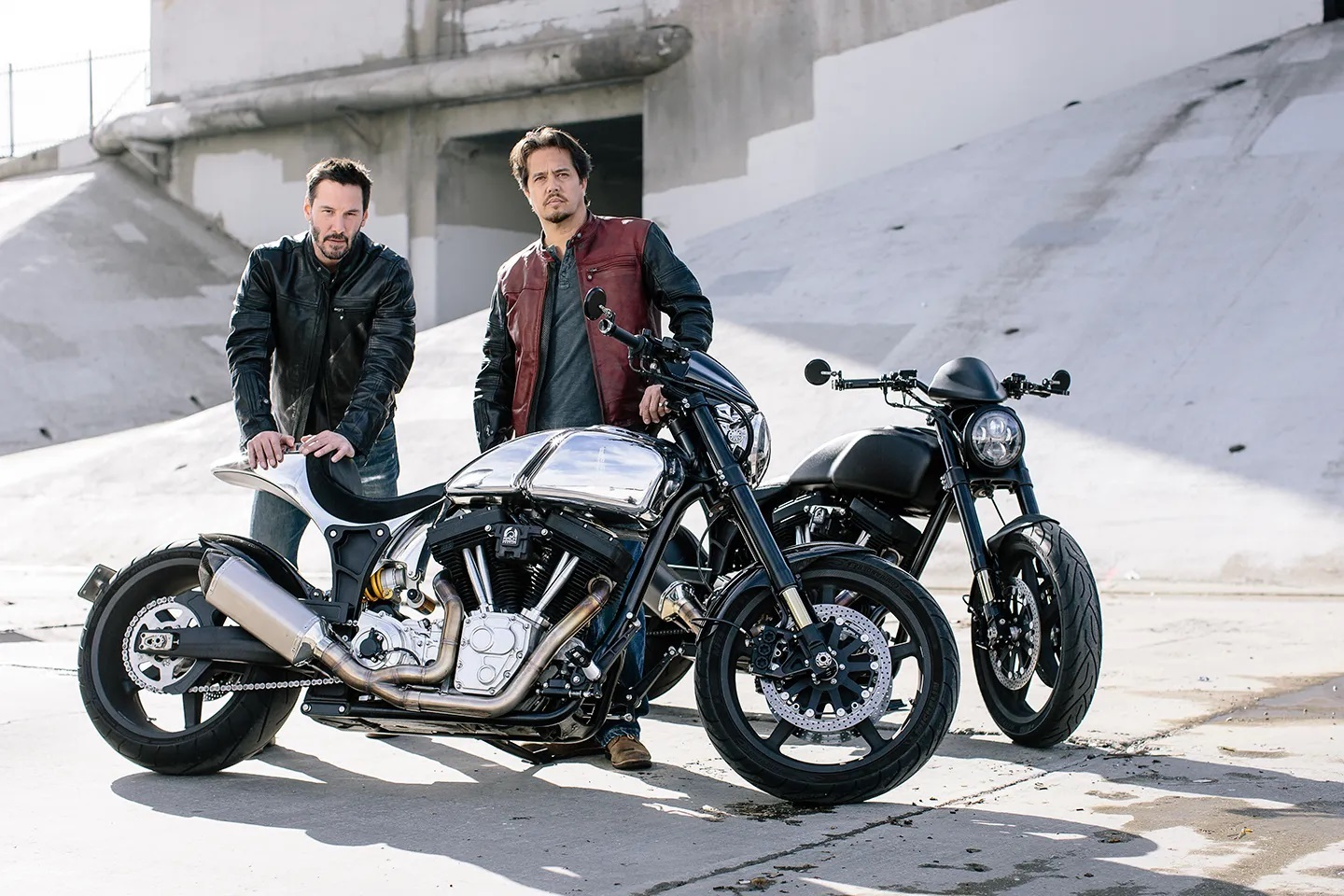A side view of Keanu Reeves and Gard Hollinger standing next to two ARCH motorcycles via IMPACT: Revitalizing the custom motorcycle scene
