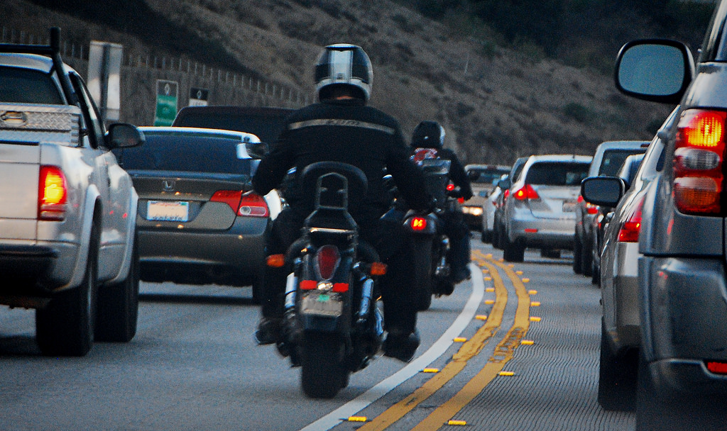 A Harley-Davidson motorcycle rider splits lanes on an American freeway