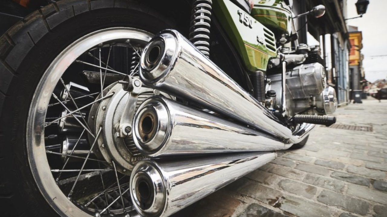 Close-up of three motorcycle exhaust pipes on a Benelli Sei 750